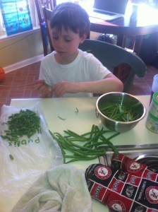 Nicholas learns the super fun art of snapping green beans.